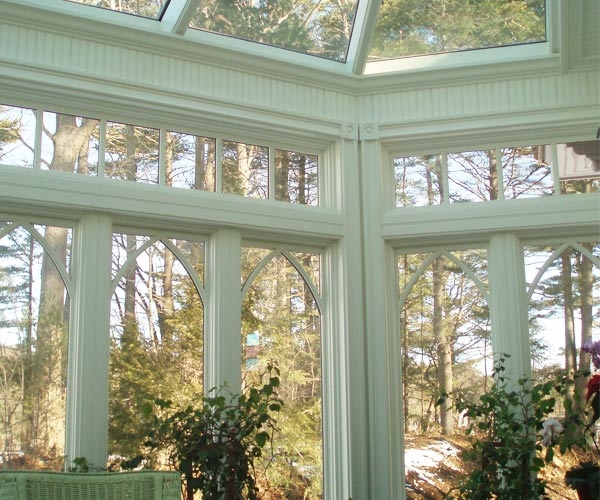 An interior view of a Victorian conservatory featuring casement windows with gothic grills and clerestory in Kittery Point, Maine