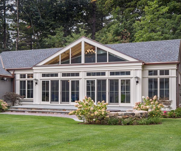 Exterior view of an indoor swimming pool enclosure with casement windows and French doors in Carlisle, Massachusetts