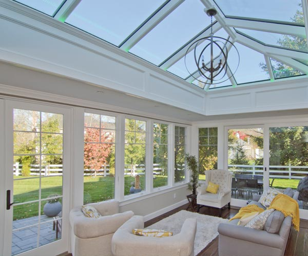 Interior view of an airy orangery with casement windows and grilled French doors in Medfield, Massachusetts