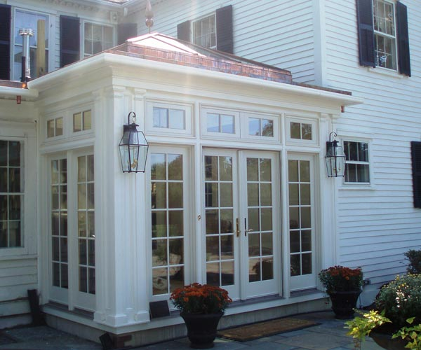 Extrerior view of an elegant colonial orangery with clerestory windows and French doors in Shrewsbury, Massachusetts