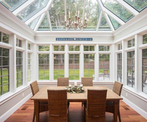 Interior view of a dining area within a traditional conservatory with casement and clerestory windows in Rye, New Hampshire