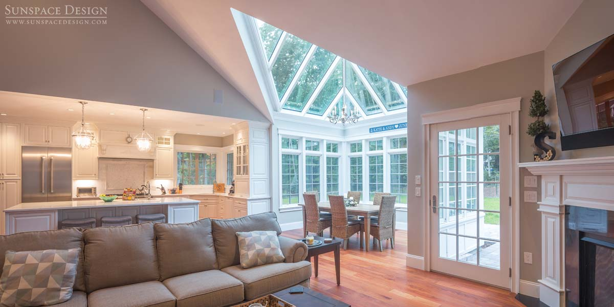 A sloped conservatory roof system located beside the foyer, family room, and kitchen of a Rye, New Hampshire home