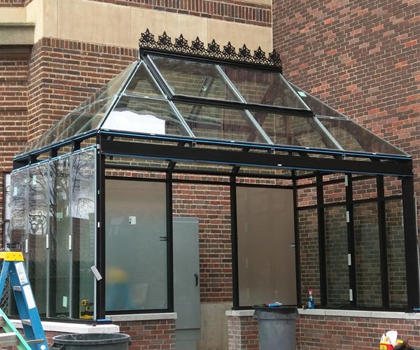 A construction site photograph of a completed greenhouse frame built with black, powder-coated aluminum