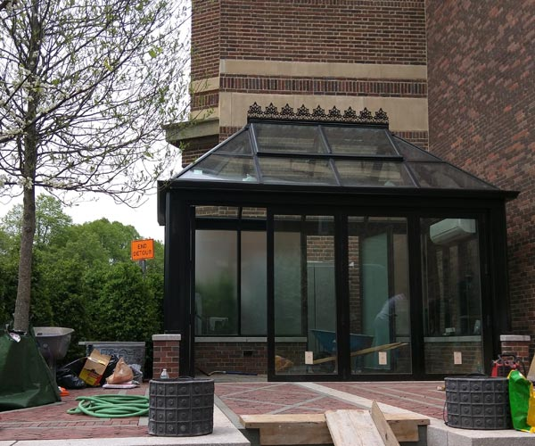 The construction crew completes work on the folding glass front wall (accordion door) of this Boston greenhouse