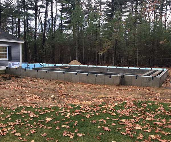 A construction photograph of a swimming pool enclosure foundation placed beside a New England carriage house