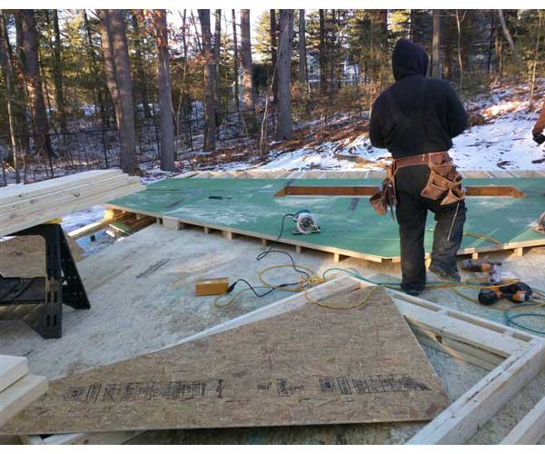 Sunspace Design crew members working on a swimmin pool enclosure's exterior frame on a snowy New England morning