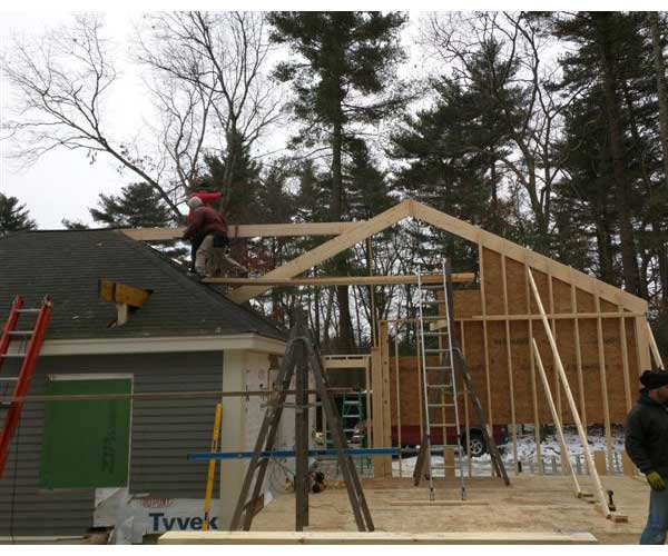 Construction workers building a gable end wall and a tie-in to an existing carriage house for a seamless transition