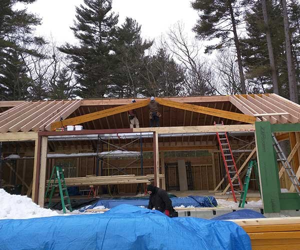 The Sunspace Design crew begins framing this Carlisle, Massachusetts swimming pool enclosure's roof, adding large structural valley rafters to create the glass roof's shape