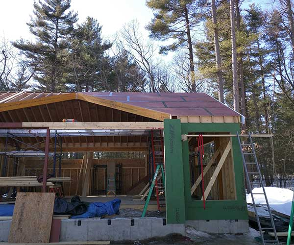 A New England pool building with sheating installed on the walls and roof