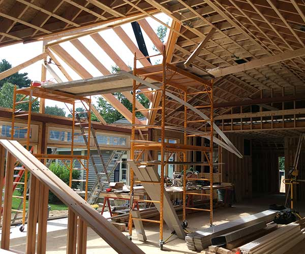 Workers install new, custom-milled douglas fir rafters into the glass roof frame in order to support the glass roof panes