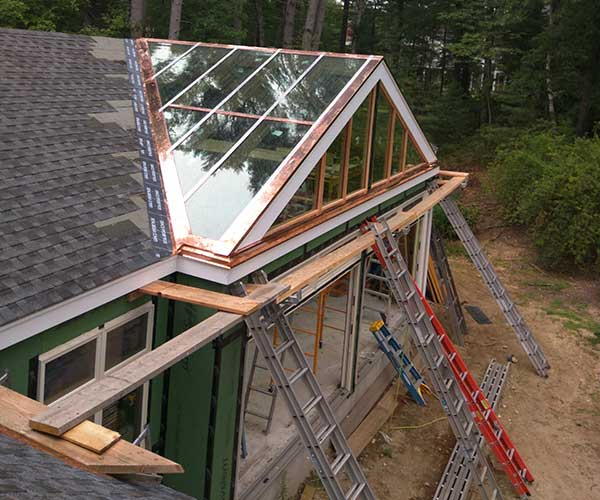 A series of ladders rest against construction staging beside a Carlisle, Massachusetts glass space construction site while copper flashing is being installed on the glass roof's exterior