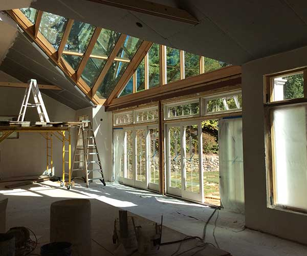 An interior photograph of a pool enclosure with a custom glass roof, sliding glass doors, and in-progress interior plaster