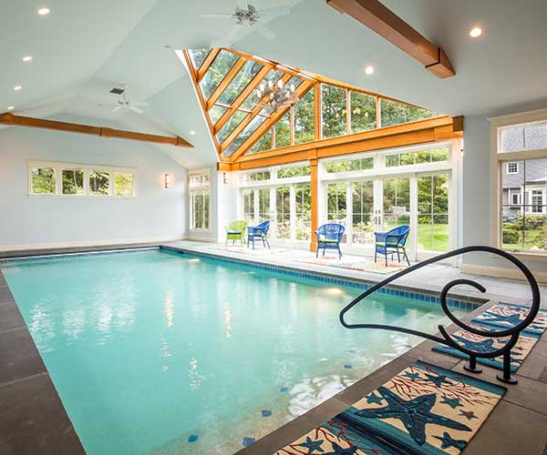 A photograph taken beside an enclosed swimming pool surrounded by pristine bluestone flooring, beneath a custom glass roof