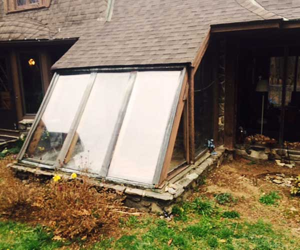 A photograph of an old, leaky sunroom that's about to be replaced by a custom Sunspace Design glass conservatory and roof system