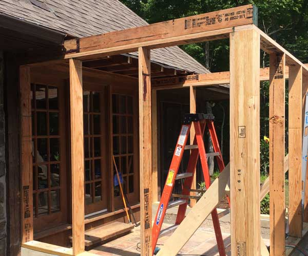 Newly-built conservatory walls are erected by Sunspace Design's team of New England crewmen on a New Hampshire residential construction site