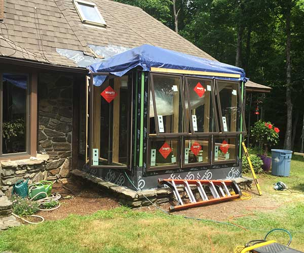 A freshly-insulated conservatory is outfitted with brand new Marvin casement windows to allow a flood of natural light into the interior