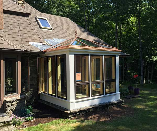 A photograph of a recently-installed glass roof (and finial) on a New England conservatory home addition
