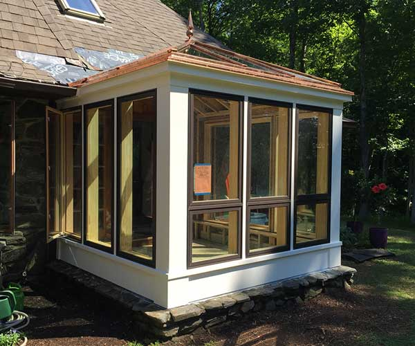 An exterior view of a New Hampshire conservatory with completed exterior composite trim in the hours before painting begins