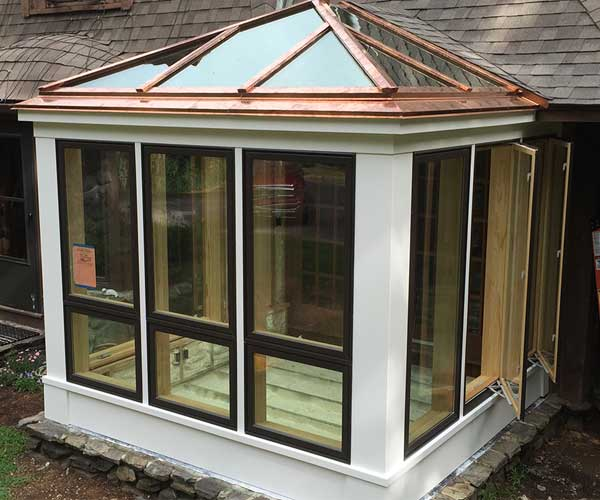 An exterior photograph of the conservatory under construction which shows recently installed copper cladding