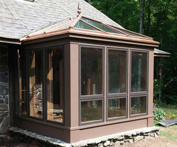 An exterior look at the conservatory with paint work completed using the existing home's color scheme