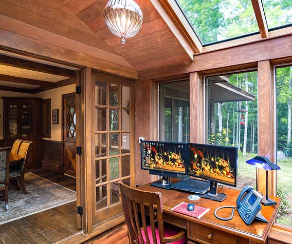 An interior view of the finished office space outfitted with natural wood inside the new custom glass conservatory