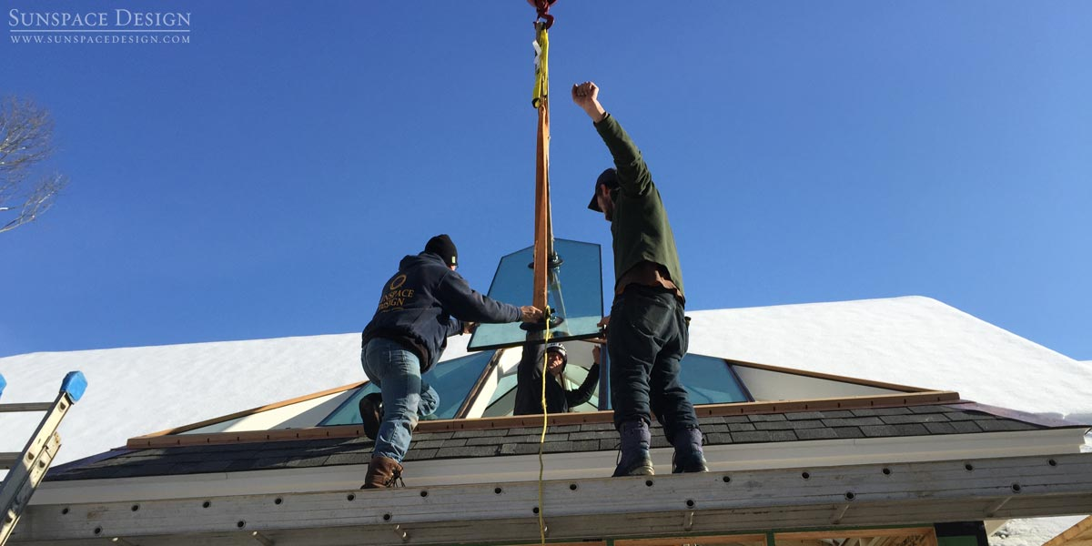 A wide photograph of Sunspace Design crewmen accepting and placing a crane-lifted glass pane for a Rye, New Hampshire conservatory glass roof system