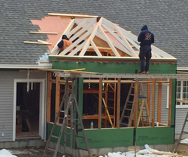 The newly installed glass roof frame sits in position above the conventionally framed walls before the glass, copper capping, and flashings are installed