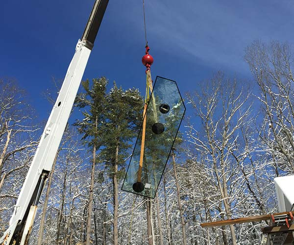 A crane operator lifts an argon-filled, low-e glass (PPG Solar Ban 70 XL) pane into position