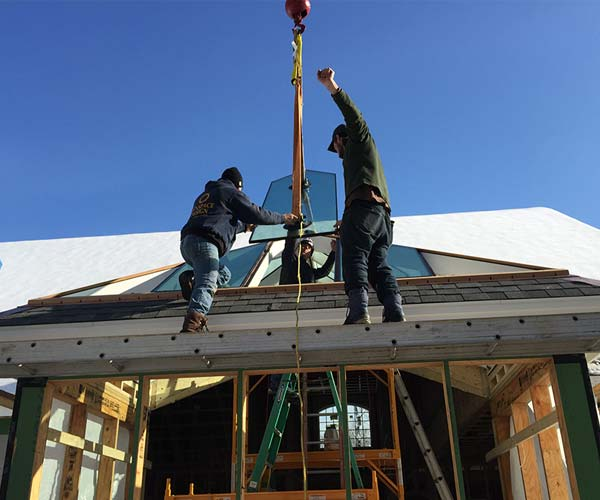 Three crewmen install this New Hampshire conservatory's largest glass roof pane, which measures in at just over eight feet in length
