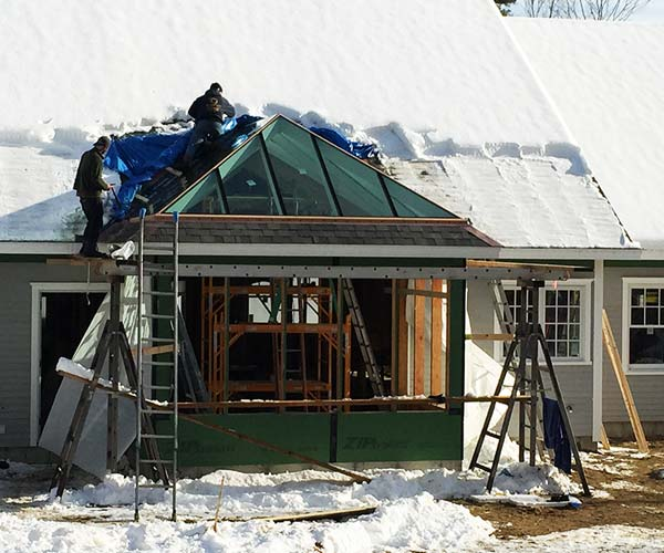 The conservatory's glass roof system has a front that is fully outfitted in high performing glass and crewmen work around a residential roof area that has been cleared of snow