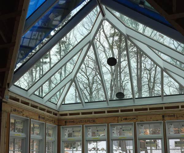 An interior view of the conservatory which depicts the installed glass roof, the steep pitch of the structure's design, and the surrounding snowy trees through the windows