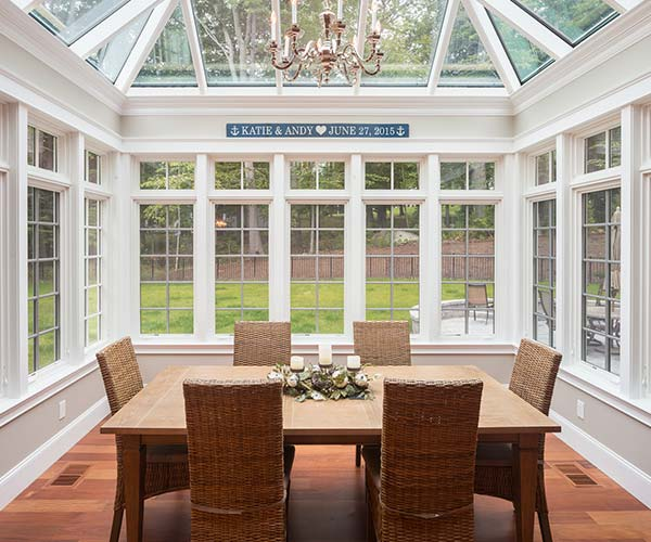 The backyard is visible through the Marvin casement windows (each with a clerestory above) lining the walls of this NH conservatory project