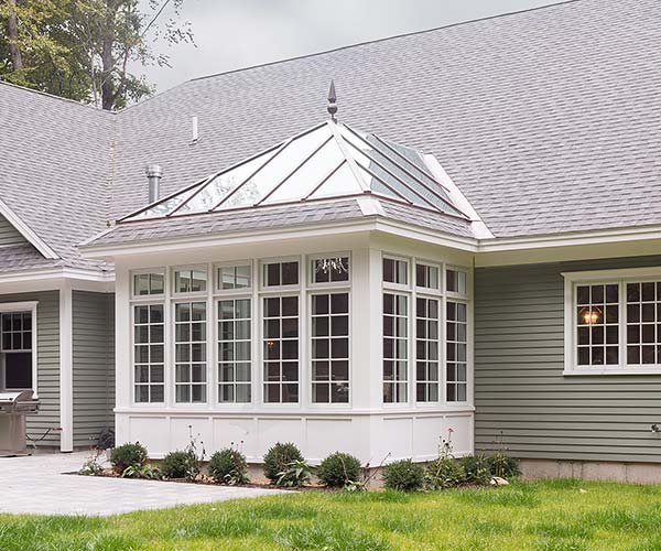 The finished conservatory stands proudly in the homeowner's yard and is surrounded by small plants