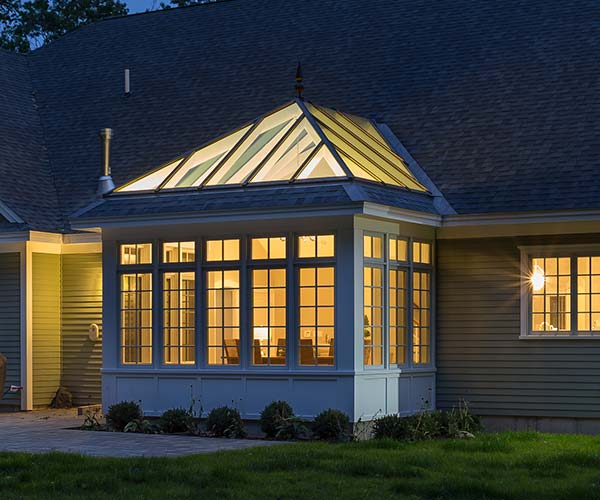 A view of the completed conservatory taken at night with interior light pooling into the yard