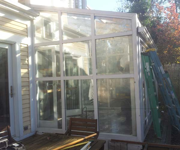 A photograph of an outdated sunroom / greenhouse structure that's to be replaced by a brand new glass conservatory