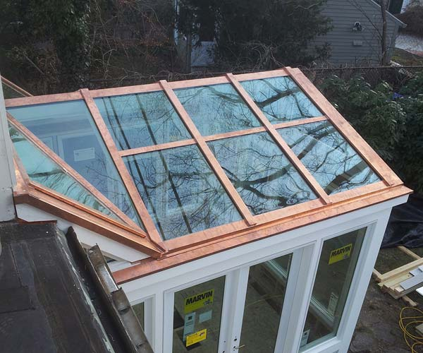 Work on the conservatory's glass roof is completed with the addition of copper caps and flashings