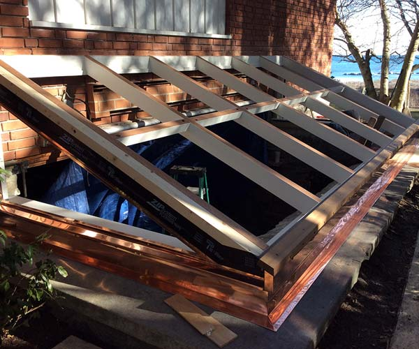 A photo of the shop-framed mahogany ground-level skylight with fresh white primer being installed on-site