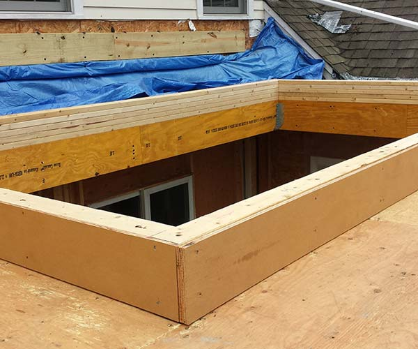 A photo of a frame that has been positioned to accept the orangery-style glass roof elements
