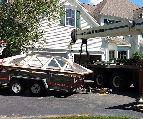 A crane operator prepares to lift the roof system into position