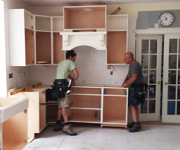 The Sunspace Design crew installs brand new kitchen cabinets as part of this home renovation project