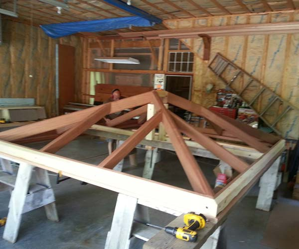 A photo of a mahogany skylight frame being developed in the Sunspace Design workshop before installation at a Shrewsbury, Massachusetts work site