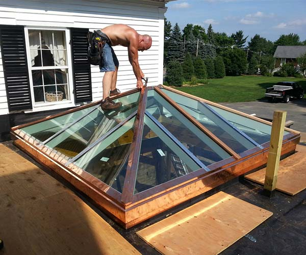 A Sunspace field crew member adds the final copper flashings to this orangery skylight system now that the high performance glass panes are installed