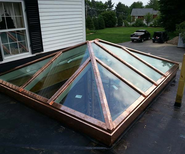 The completed glass roof system with copper flashings shines in the sunlight