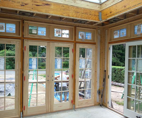 An interior view of the orangery's structural framing with Sunspace crew visible through the French doors