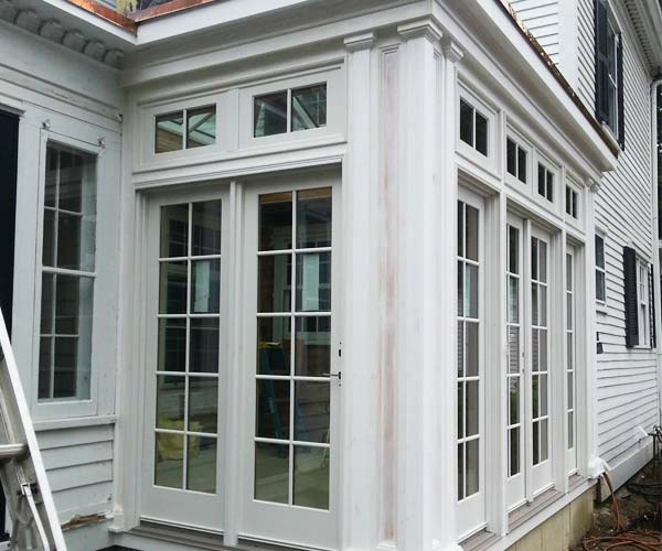This orangery's columns feature stately details and an intricate design that blends with the existing home's colonial-style architecture