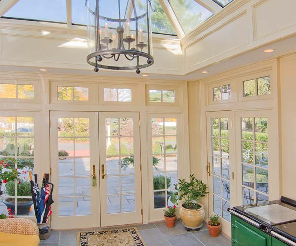 The French doors, glass skylight, and tall windows of this residential orangery create a warmly-lit entryway