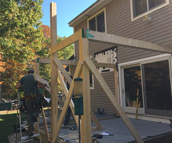 A photo of a Sunspace crewman constructing a new wall frame and structural headers on the rear deck of the client's home