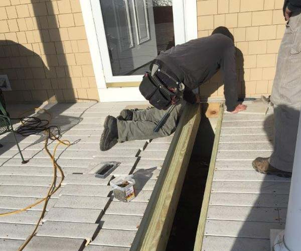 A Sunspace worker is on his hands and knees removing decking in anticipation of installing a carrying beam below
