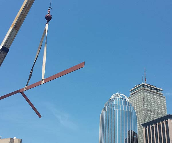 A crucial steel ridge beam is being hoisted into position on the rooftop with a view of the Boston city skyline visible in the background