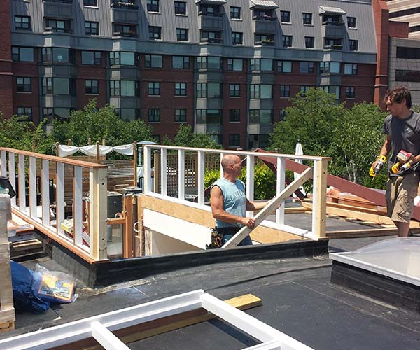 Workers have installed the side walls of the glass skylight's mahogany frame; rows of city apartment buildings are visible in the background